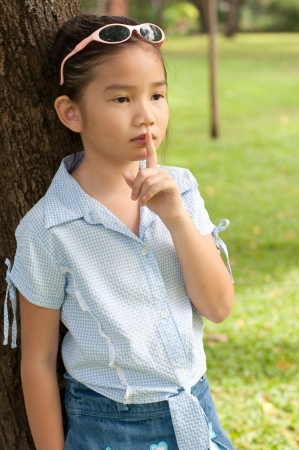 Portrait of beautiful little asian girl in the park,  she make finger on lips, Thailand.