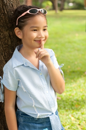 Portrait of beautiful little asian girl in the park,  she make finger on lips, Thailand. photo