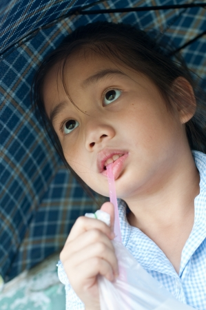 Head shot portrait of beautiful little asian girl in the park, she is thinking, Thailand. photo
