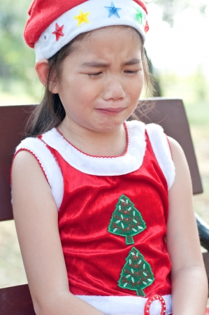 Beautiful young Thai  girl in santa hat and red suit, Thailand. photo