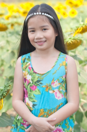 Beautiful Thai girl in blue dress at sunflower field, Thailand. photo