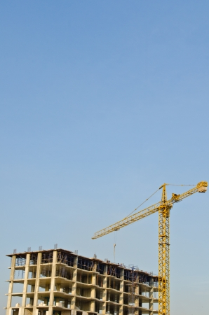 Tower crane and building structure with blue sky, Thailand.