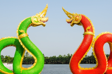 Green and red Naga statue on blue sky, Thailand photo