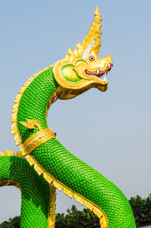 Green Naga statue on blue sky, Thailand photo