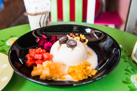 black dish: Cold tofu pudding with fruit and dessert on black dish, Thailand.