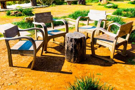 Wooden chairs set in park, Thailand.