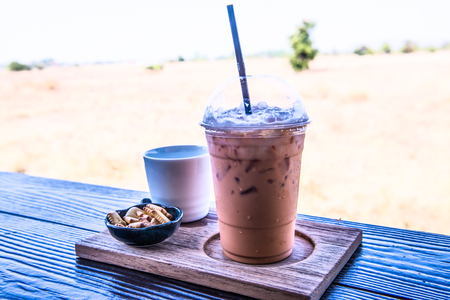 Iced Milk Tea with biscuit on Wooden Table, Thailand Stock Photo