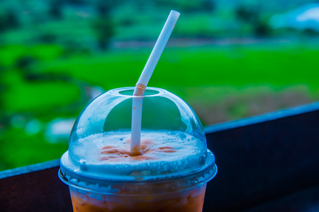 Iced Milk Tea in Plastic Glass with Natural View, Thailand.