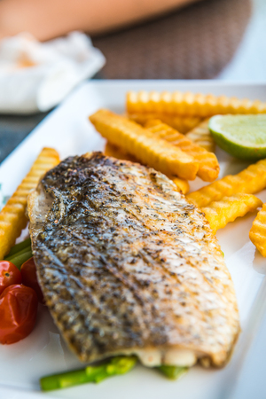 Grilled salted snapper with french fries on white plate, Thailand.