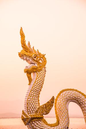 White Naga statue at Kwan Phayao with evening sun, Thailand.