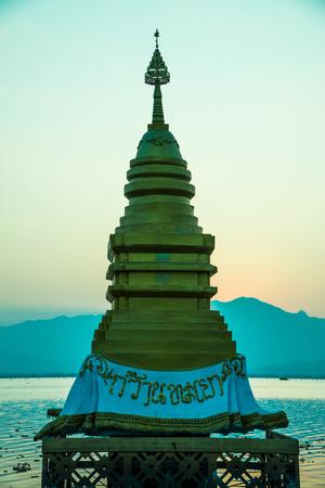 Golden stupa in Kwan Phayao with evening sun, Thailand.