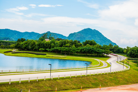Green grass yard with lake, Thailand. Stock Photo