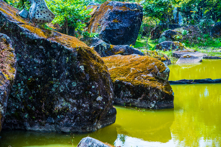 chiangmai province: Ancient stone with green lake at Chiangmai province, Thailand. Stock Photo