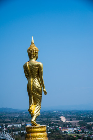 spiritual architecture: Walking golden buddha statue at Phra That Khao Noi temple, Thailand.