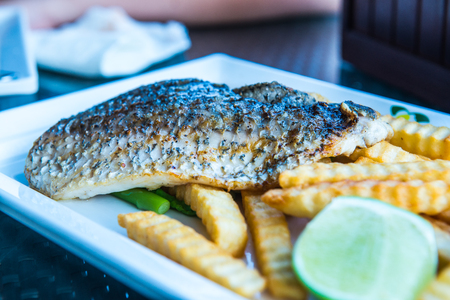 grill: Grilled salted snapper with french fries on white plate, Thailand.