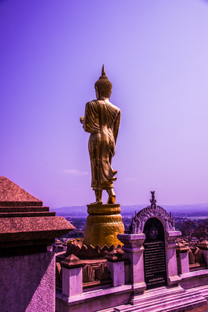 Walking golden buddha statue at Phra That Khao Noi temple, Thailand.
