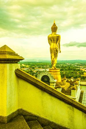 Walking buddha statue at Phra That Khao Noi temple, Thailand.