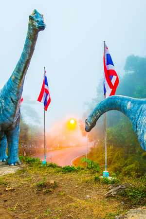 Statue of Chiang Muan dinosaur with curve road, Thailand.