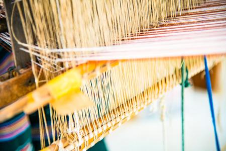 Native thread on Thai traditional weaving machine, Thailand. Stock Photo