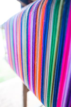 Colourful threads on an ancient wooden loom, Thailand. Standard-Bild - 124615251
