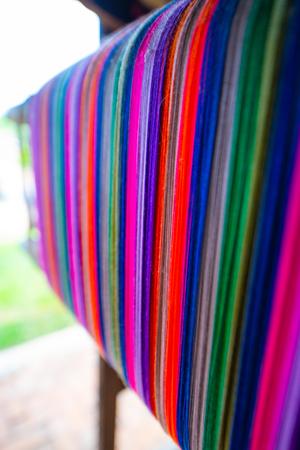 Colourful threads on an ancient wooden loom, Thailand. Standard-Bild - 124615432
