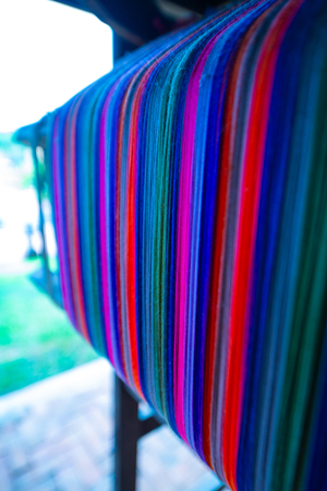 Colourful threads on an ancient wooden loom, Thailand. Standard-Bild - 124619400