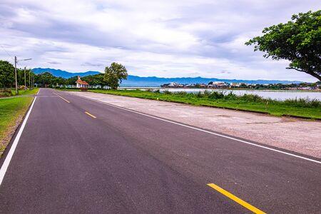 Road and running track beside Kwan Phayao lake, Thailand.