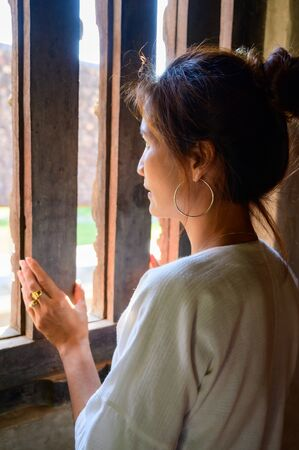 Thai woman in Thai native dress beside the window, Chiang Mai. Stok Fotoğraf