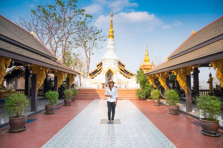Asian woman with Wat Phra That Doi Phra Chan background, Lampang province.