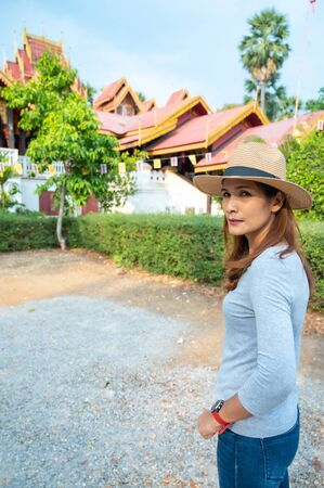 Asian woman with Wat Sri Rong Muang background in Lampang province, Thailand.