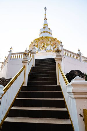 White pagoda with stair walkway at Tham Phra Sabai temple, Lampang province.