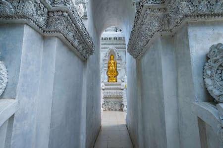 Temple entrance and golden Buddha statue at San Pa Yang Luang temple, Lamphun province.
