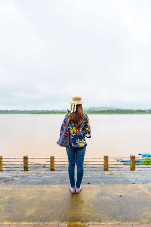 A Woman Traveler with Mekong River Background at Golden Triangle, Chiang Rai Province.