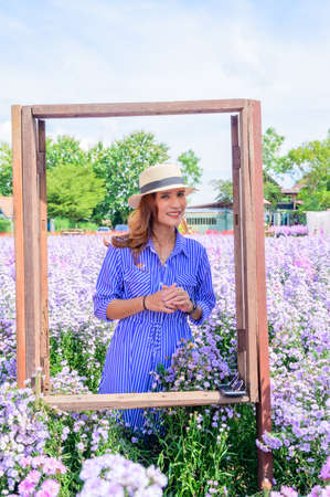 Thai Woman in Frame with Beautiful Flower Garden at Chiang Mai Province, Thailand.
