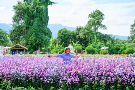 Thai Woman with Beautiful Flower Garden at Chiang Mai Province, THailand.