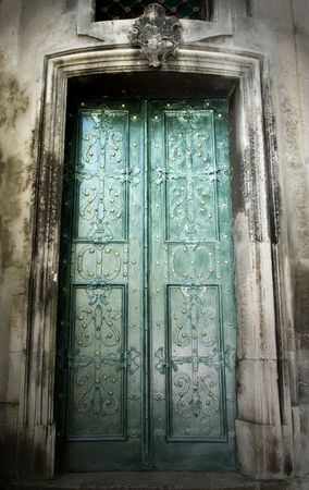 closed green metalic doors with ornament at old stone building