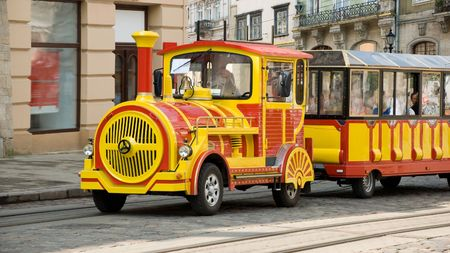 yellow red excursion train with wagon in old town