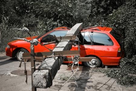 electric post fallen onto red car Standard-Bild