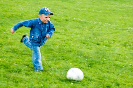 smiling boy in blue jeans playing football on green field Stock Photo