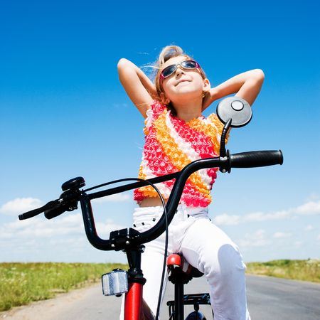 girl sits on bicycle at sunny day  Stock Photo