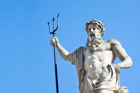 neptune statue on blue sky background photo
