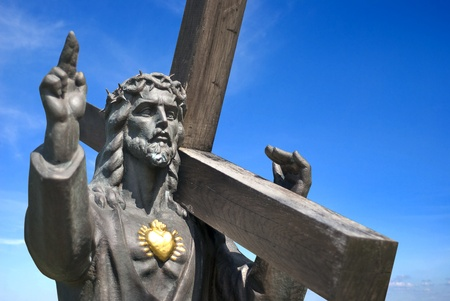 jesus with golden heart holding cross on blue sky background