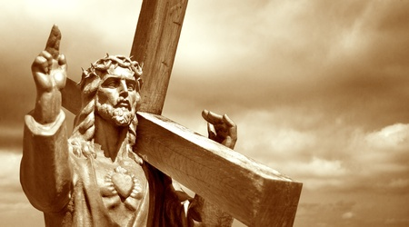 jesus holding cross on cloudy sky background