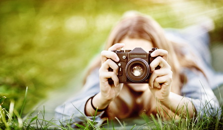 girl photographer makes a photo lying in the grass Stock Photo