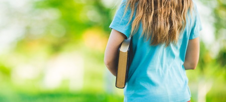 girl in a blue t-shirt holding a book on blurry background Stock Photo