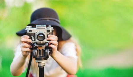 girl makes a photo on retro camera on tripod Stock Photo