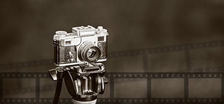retro photo camera on tripod  on dark blurry background Stock Photo