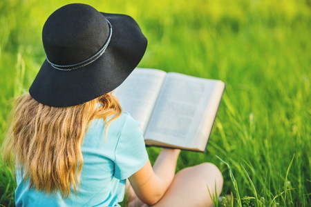 girl  sits on a grass and reads a book