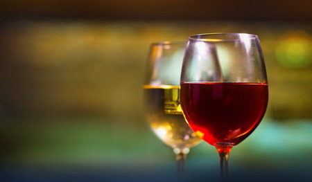 Two glasses of red and white wine on blurred background. Stock Photo