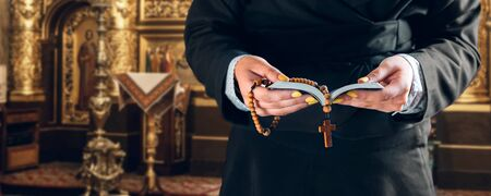 female hands hold prayer book and rosary in a church